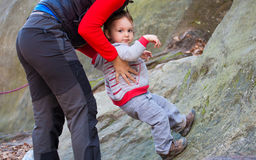 A child tries to climb on the rock. Stock Photo