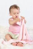 Child tries to dress oneself #1. Baby girl tries to dress oneself Stock Photo