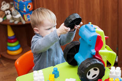 Child tries to fix a broken toy tractor. Indoor Royalty Free Stock Photography