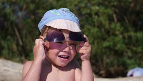 The child tries to wear sunglasses. The beach, a Sunny hot day stock footage