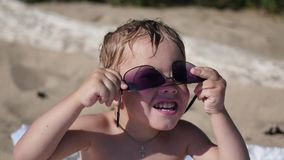 The child tries to wear sunglasses. The beach, a Sunny hot day stock video footage