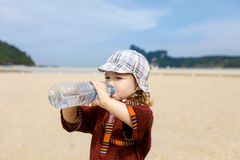 Child on tropical beach, drinking bottled water Stock Images