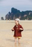 Child on tropical beach, eating bread stock photo