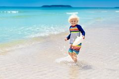 Child on tropical beach. Sea vacation with kids. Stock Photos