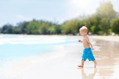 Child on tropical beach. Sea vacation with kids. Child on beautiful beach. Little boy running and jumping at sea shore. Ocean vacation with kid. Children play Royalty Free Stock Photography
