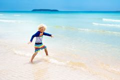 Child on tropical beach. Sea vacation with kids. Child on beautiful beach. Little boy running and jumping at sea shore. Ocean vacation with kid. Children play Stock Photography