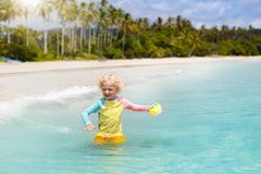 Child on tropical beach. Sea vacation with kids. Child on beautiful beach. Little boy with toy boat running and jumping at sea shore. Ocean vacation with kid Stock Photo