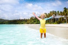 Child on tropical beach. Sea vacation with kids. Child on beautiful beach. Little boy with toy boat running and jumping at sea shore. Ocean vacation with kid Stock Photography