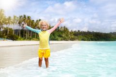 Child on tropical beach. Sea vacation with kids. Child on beautiful beach. Little boy with toy boat running and jumping at sea shore. Ocean vacation with kid Royalty Free Stock Images