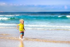 Child on tropical beach. Sea vacation with kids. Child on beautiful beach. Little boy running and jumping at sea shore. Ocean vacation with kid. Children play Royalty Free Stock Photo