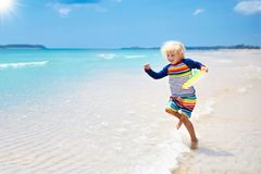 Child on tropical beach. Sea vacation with kids. Child on beautiful beach. Little boy running and jumping at sea shore. Ocean vacation with kid. Children play Stock Photos