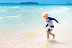 Child on tropical beach. Sea vacation with kids. Child on beautiful beach. Little boy running and jumping at sea shore. Ocean vacation with kid. Children play Stock Images