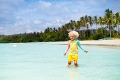 Child on tropical beach. Sea vacation with kids. Child on beautiful beach. Little boy with toy boat running and jumping at sea shore. Ocean vacation with kid Stock Images