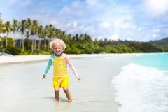 Child on tropical beach. Sea vacation with kids. Child on beautiful beach. Little boy with toy boat running and jumping at sea shore. Ocean vacation with kid Stock Image