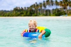 Child on tropical beach. Sea vacation with kids. Child with inflatable ring on beautiful beach. Little boy swimming in exotic sea. Ocean vacation with kid Stock Photos