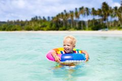 Child on tropical beach. Sea vacation with kids. Child with inflatable ring on beautiful beach. Little boy swimming in exotic sea. Ocean vacation with kid Stock Image