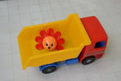 Child truck carries a flower. Toy for small children, plastic car. On the back of the car is a plastic flower with painted eyes royalty free stock image