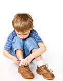 Child try to tie shoelaces. Young boy try to tie shoelaces stock photos