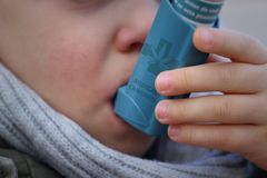 Child trying asthma with cannabis inhaler stock photo