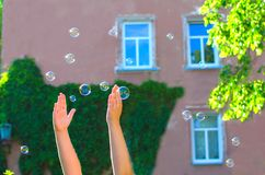 Child trying to catch the soap bubbles flying all around. Hands of children trying to destroy soap bubbles on the street royalty free stock photography