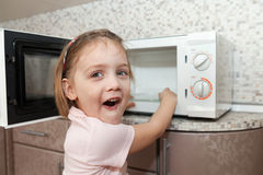 Child  trying to turn on  microwave Stock Image