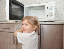 Child  trying to turn on  microwave Royalty Free Stock Photos