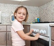 Child  trying to turn on stove Stock Images