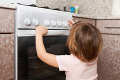Child  trying to turn on stove Royalty Free Stock Photography