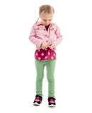 Child trying to zip her pink coat, isolated Stock Images