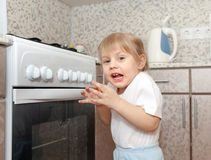 Child  trying   turn on stove Royalty Free Stock Photo