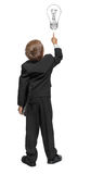 Child  in a tuxedo pointing at wall. Stock Image