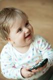 Child with tv remote control. A baby laughs as she holds a television remote control Royalty Free Stock Photography