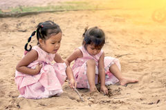 Child two asian little girls playing with sand in playground Royalty Free Stock Images