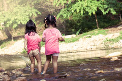 Child two girls having fun to play in waterfall together Stock Image