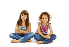 A child, two girls sitting on the floor. Isolated on white background Royalty Free Stock Image