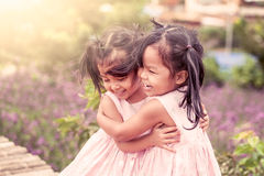 Child two happy little girls hug each other with love. In the flower garden in vintage color tone Royalty Free Stock Photography