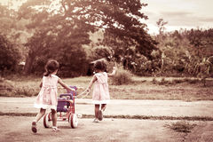 Child two little girls having fun to pull her tricycle. And running together in the park,vintage color filter Royalty Free Stock Photography
