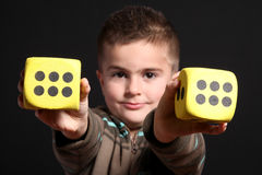 Child with two yellow dices Stock Images