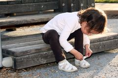 Child tying her shoe. While sitting at the playground stock photography