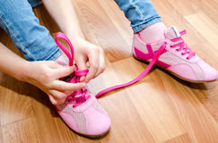 Child tying her shoes sitting on the floor at home Royalty Free Stock Image