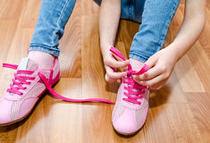 Child tying her shoes sitting on the floor at home Stock Image