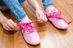 Child tying her shoes sitting on the floor at home Royalty Free Stock Photo