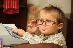 Child with typewriter. Cute little child with funny glasses writing on typewriter royalty free stock photography