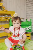 Child in Ukrainian national costume with chick on her head. Stock Photography