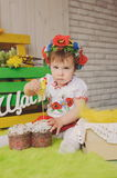 Child in Ukrainian national costume with Easter cake. Text happiness. Royalty Free Stock Photos