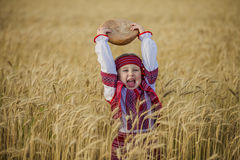 Child in Ukrainian national costume. With a loaf of bread in his hand stock photos