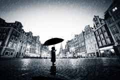 Child with umbrella standing alone on cobblestone old town in rain Stock Image