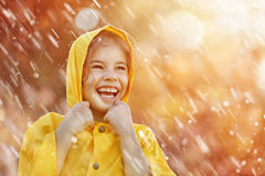 Child under autumn rain. Happy funny child under the autumn shower. Girl is wearing yellow raincoat and enjoying rainfall royalty free stock images