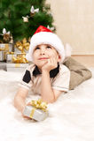 Child under the Christmas tree with gifts Stock Photos