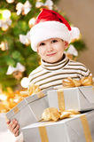 Child under the Christmas tree with gifts Stock Images